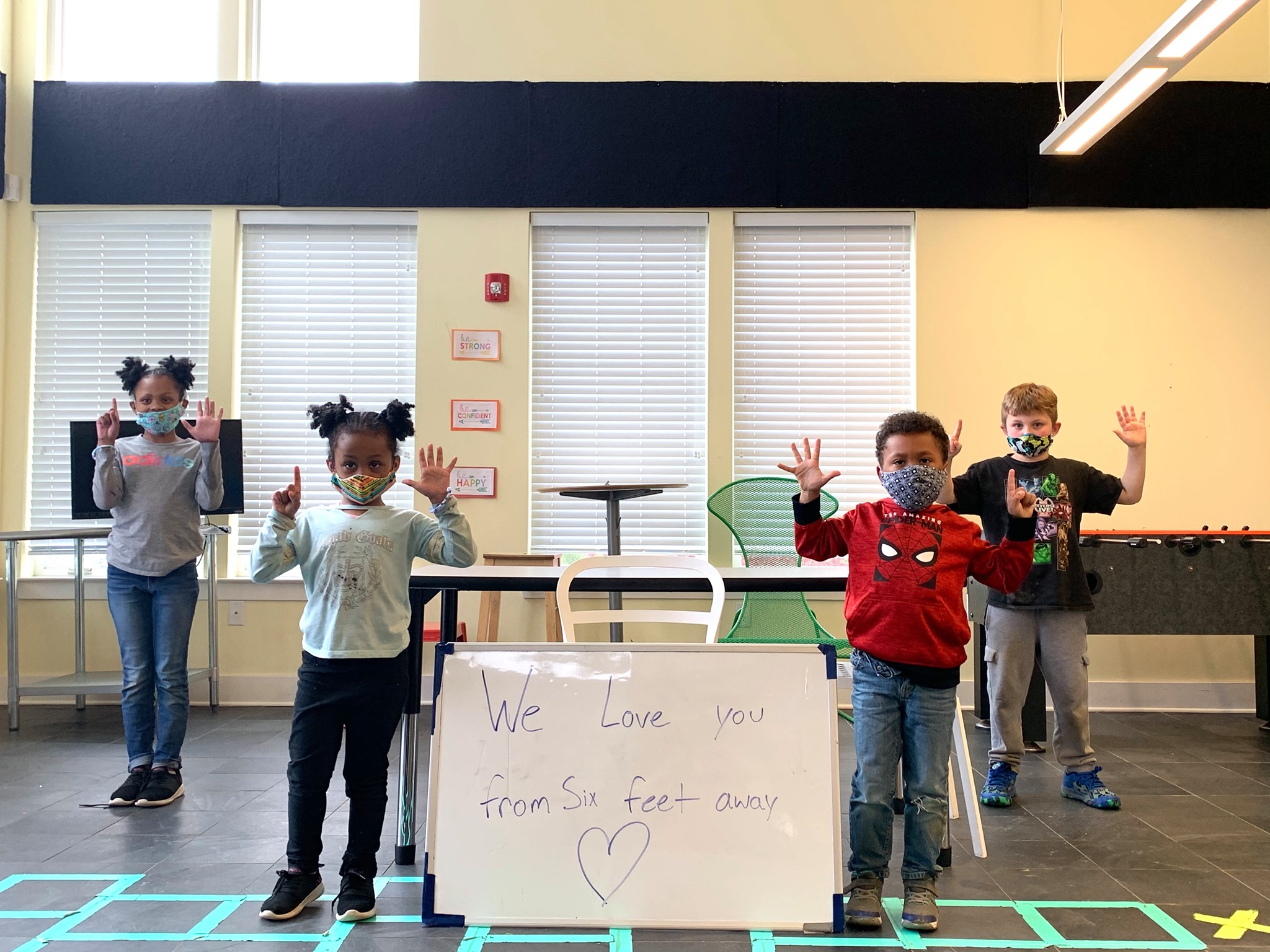 """Children in masks holding six fingers up. Sign reads """"we love you from six feet away."""""""