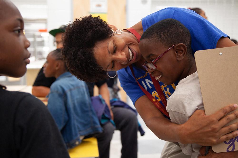 adult teacher hugging a student