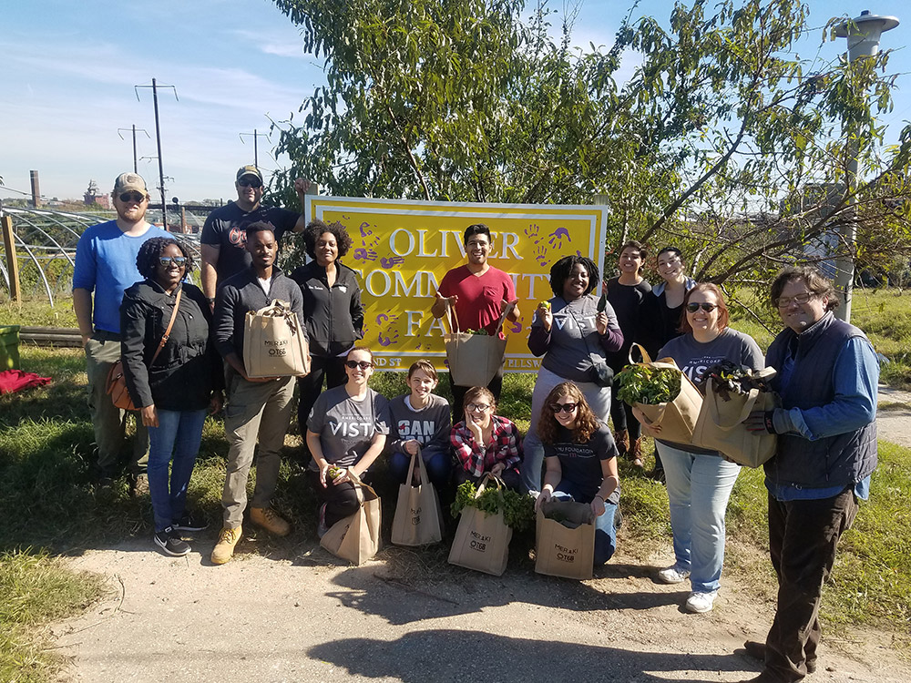 vista members holding bags of produce outside of a farm