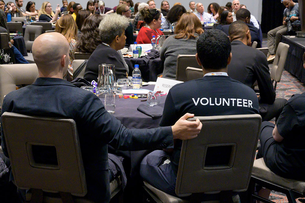 volunteers sit at a table watching a speaker on stage