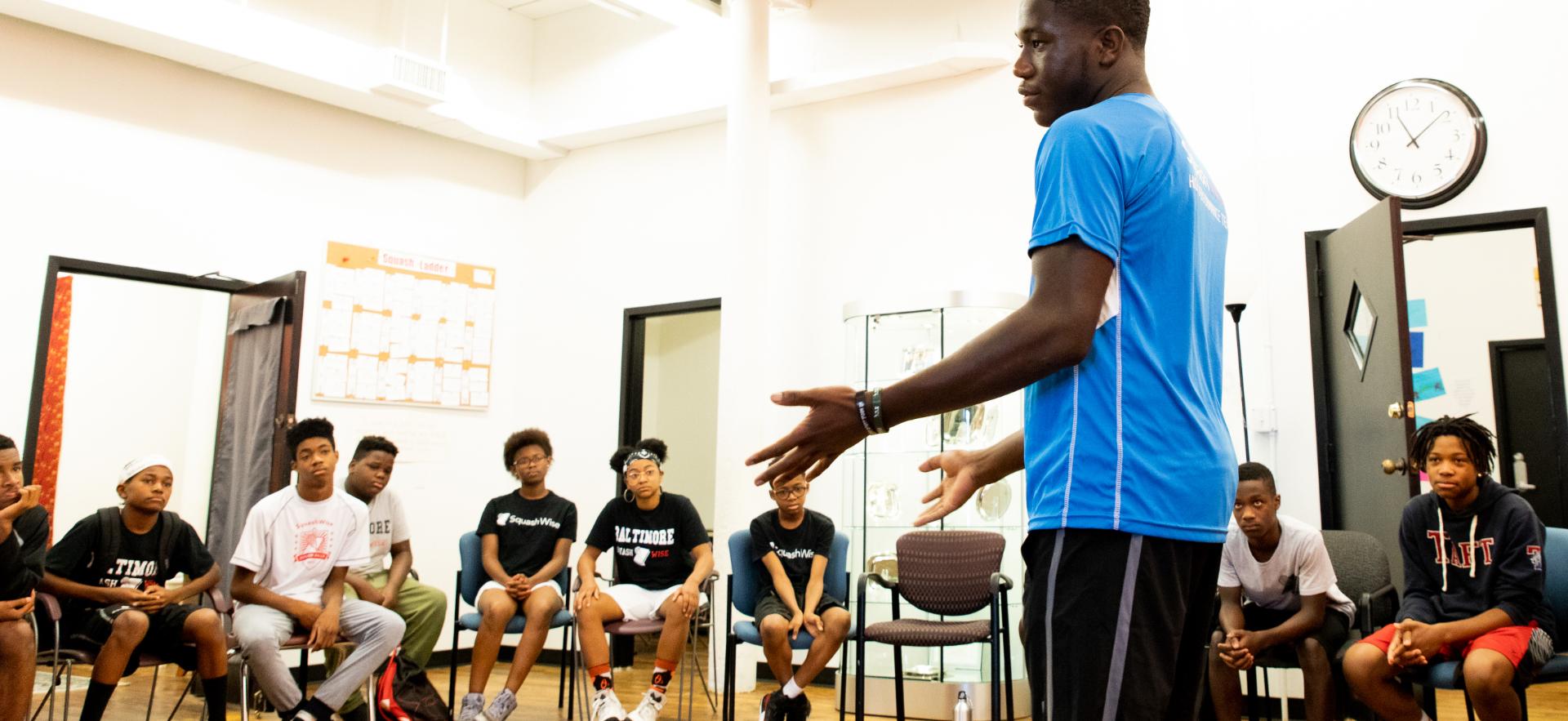 man addressing room full of sitting students