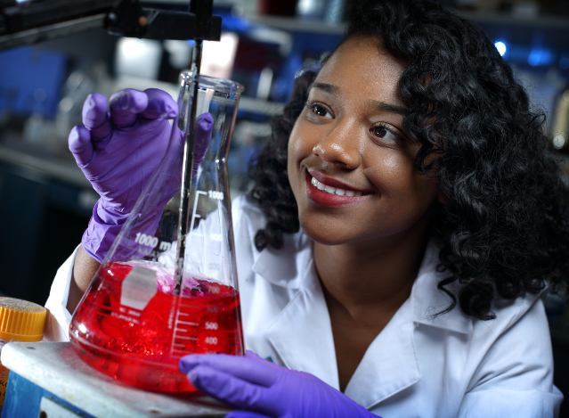woman smiling while looking at a beaker full of red liquid